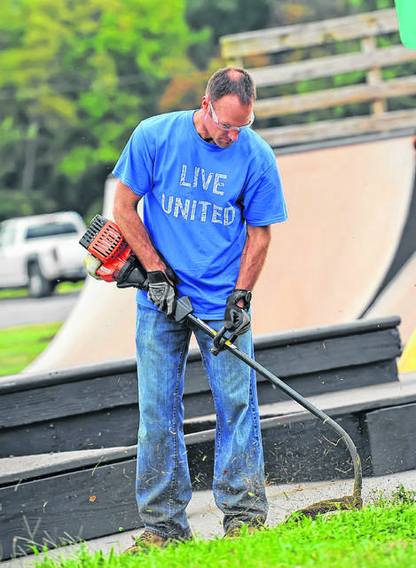 Jim Morrisey trims grass around the skate park at Faurot Park on the United Way Day of Caring last year. The community-wide volunteer day is one of the organization's largest events.