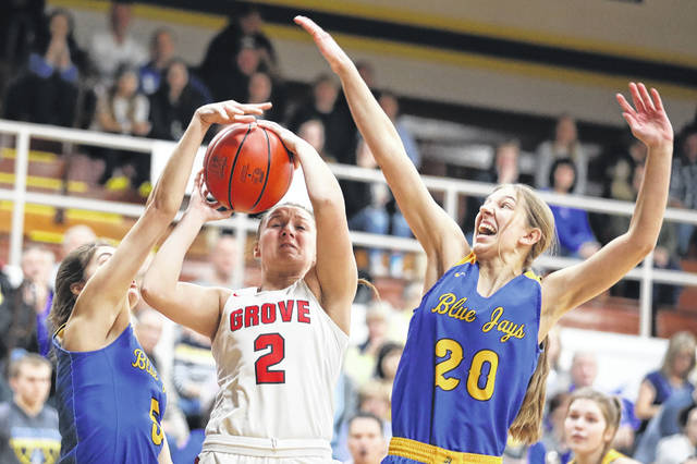 Melanie Koenig, left, and Hannah Will of Delphos St. John's defend a shot by Columbus Grove's Angel Schneider during Thursday night's Division IV district semifinal at Ottawa-Glandorf. Amanda Wilson | The Lima News