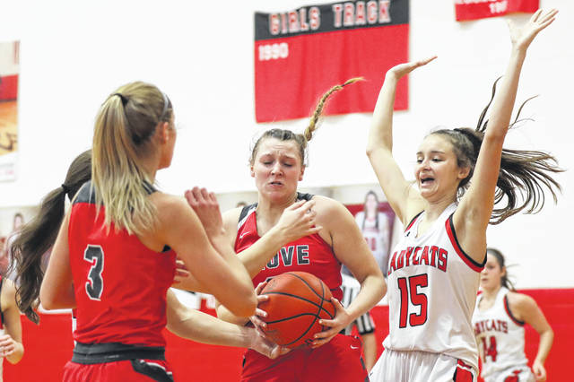Columbus Grove's Angel Schneider tries to keep control of the ball as Delphos Jefferson's Delaney Deuel (15) defends during Saturday's game in Delphos.