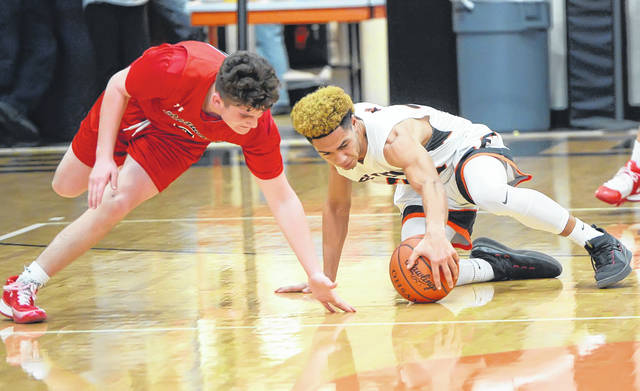 Shawnee's John Barker, left, and Elida's Devon Barnett compete for a loose ball during Friday night's game at the Elida Fieldhouse.