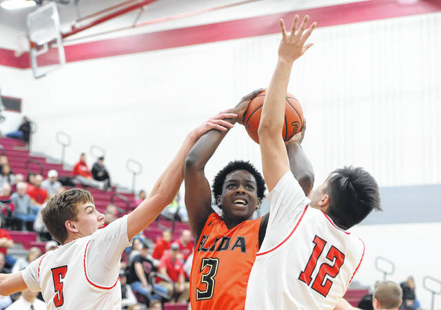 Elida's Quan Moore puts up a shot against Wauseon's Jonas Tester, left, and Noah Tester during a Friday night Division II sectional final game at Lima Senior. Richard Parrish | The Lima News