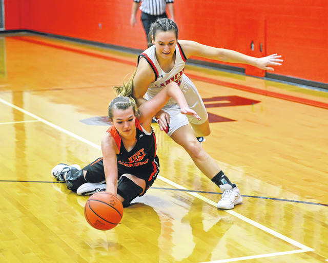 Fort Jennings' Maddison Dickaman, left, and Delphos Jefferson's Addy Stewart go to the floor for a loose ball during Monday's game at Delphos Jefferson High School.