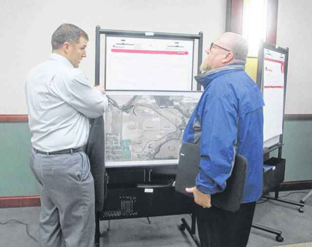Greg Bockrath & Associates, left, discusses plans for a diversion channel in Ottawa with Michael Lammers, Putnam County Commissioner, during a meeting Tuesday.