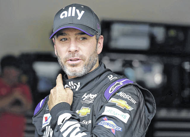 FILE - In this Feb. 16, 2019, file photo, Jimmie Johnson leaves his garage after NASCAR auto racing practice at Daytona International Speedway in Daytona Beach, Fla. NASCAR's season officially opens Sunday, Feb. 16, 2020, with the Daytona 500 at Daytona International Speedway. (AP Photo/Terry Renna, File)