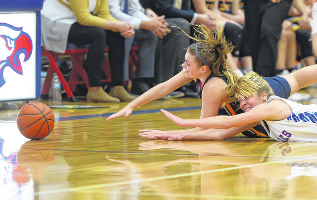 Ottawa-Glandorf's Kelsey Erford,left, and Liberty-Benton's Brooke Deeter go to the floor in while chasing down a loose ball during Saturday's game at Liberty-Benton.