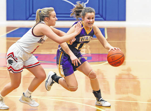 Leipsic's Marisa Hermiller drives against McComb's Alexis Shoop during a Tuesday night Division IV sectional semifinal at Patrick Henry.