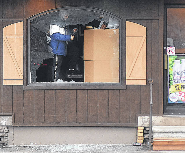 Workers cover the shattered front window at Levels Lounge at 122 E. North St. in Lima Tuesday morning after a shooting where three people died.
