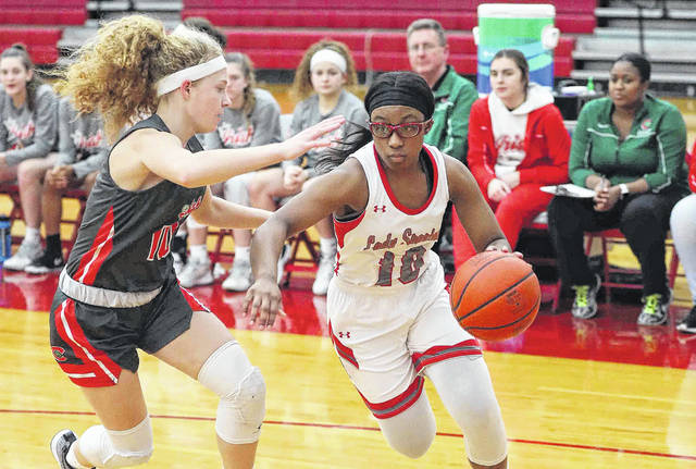 Lima Senior's Nakiya Sigman drives against Toledo Central Catholic's Ellie Hire during Thursday night's game at Lima Senior.