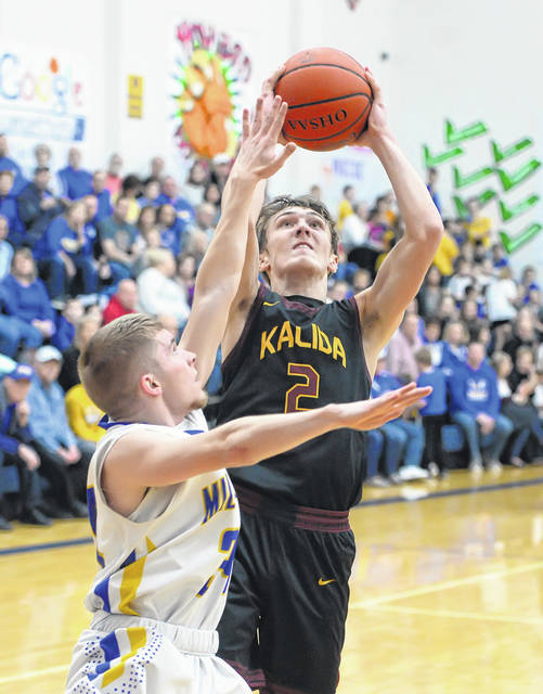 Kalida's Zach VonderEmbse puts up a shot against Miller City's Zach Fillinger during Friday night's game at Miller City.