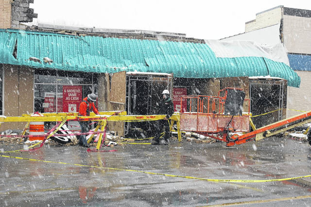 Workers place barricades in front of Rent-A-Center and American Family Insurance after a facade collapsed.