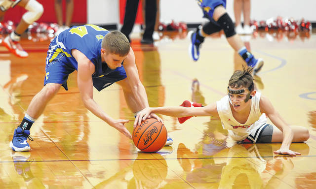 Miller City's Zach Fillinger, left, and Perry's Joey Hoersten compete for the ball during Tuesday night's game at Perry.