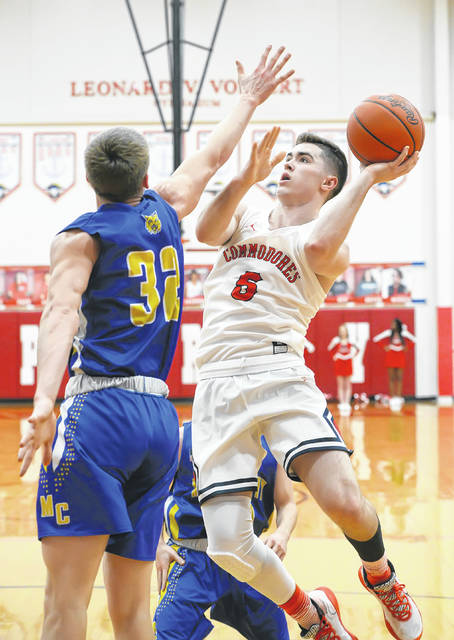 Perry's Ryan Yingst puts up a shot against Miller City's Jon Burgei during Tuesday night's game at Perry.