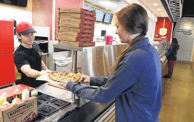 Sean McDonald, of Rapid Fired Pizza in Lima, serves Claire Pape her pizza order on Thursday afternoon. Pape is from New Bremen.