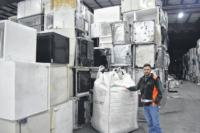 Dylan Curtis, manager of the Lima Reclaim plant on East Fourth Street, stands amid stacks of used refrigerators that are awaiting deconstruction and, ultimately, an environmentally safe final disposal.