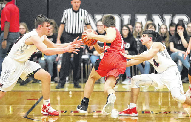 Kenton's Jayden Cornell drives against Shawnee's George Mangas, left, and Brady Wheeler during Friday night's game at Shawnee.