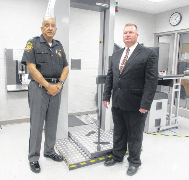 Miguel Ortiz, Putnam County Sheriff's Office jail administrator, and Brian Siefker, Putnam County sheriff, look at computer screens that are part of a body scanner system.