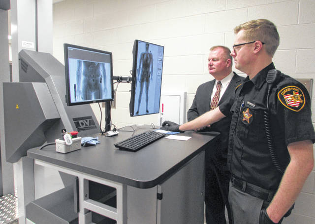 From left are Brian Siefker, Putnam County sheriff, and Travis Mangas, Putnam County Sheriff's Office correctional officer, use a body scanner that was purchased recently.