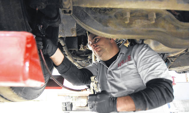 Dave Mitchell, a mechanic for the Lima schools bus garage, performs maintenance work on a school bus. The district buses 1,675 students daily.
