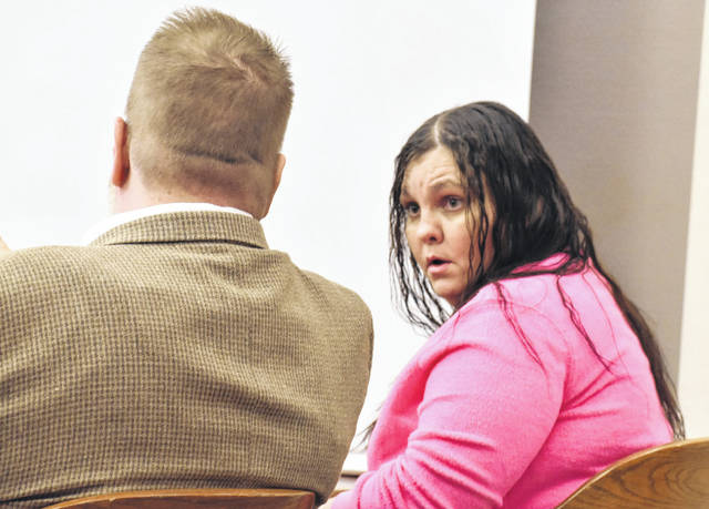 Julia Slayton, 35, of Lima, confers with her attorney, Steve Chamberlain, as her jury trial got underway Tuesday in Allen County Common Pleas Court. Slayton is charged with discharging a weapon into a habitation, a second-degree felony.