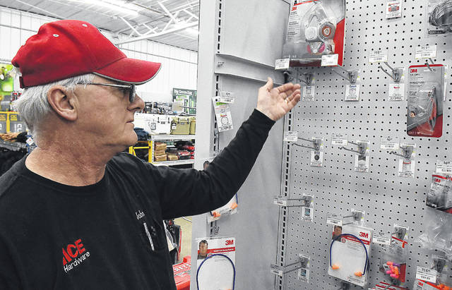 John Merricle, an employee at Elida Road Ace Hardware, points to empty displays of sold out N-95 masks. Earlier this week, mask manufacturer 3M announced it is having trouble keeping up with global demand.
