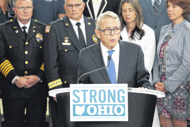 Gov. Mike DeWine unveils a bill outlining steps to curb gun violence in Ohio during a news conference Monday in Columbus. [Joshua A. Bickel/The Columbus Dispatch]