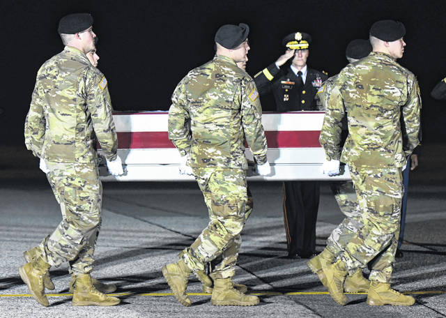 An Army carry team moves a transfer case containing the remains of Spc. Branden Tyme Kimball, early Friday at Dover Air Force Base, Delaware. Kimball, 21, died at Bagram Airfield, Afghanistan, from a non-combat related incident.  (AP Photo/Steve Ruark)