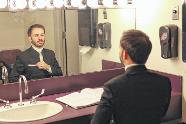 Conductor Andrew Crust adjusts his suit in his dressing room before he performed with The Lima Symphony Orchestra on Saturday evening. Amanda Wilson | The Lima News