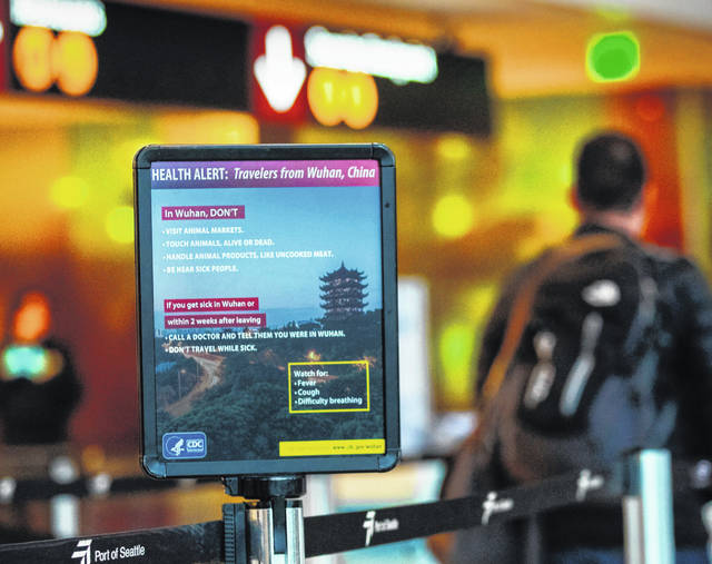 A passenger walks past a sign showing a health alert on the coronavirus near a security checkpoint at Washington state's Sea-Tac International Airport.