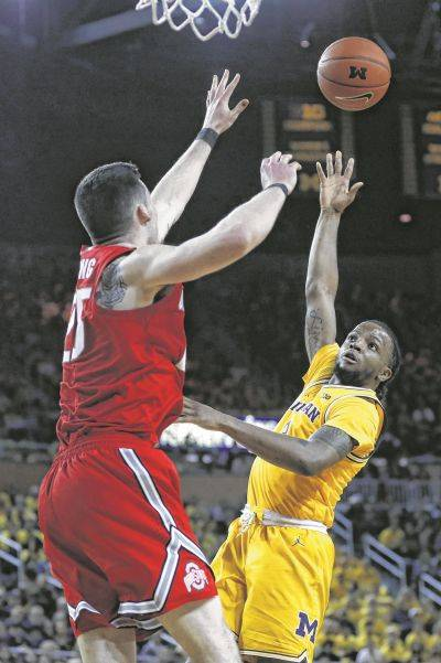 Michigan's Xavier Simpson, a Lima Senior graduate, puts up a shot against Ohio State's Kyle Young during Tuesday night's game in Ann Arbor, Mich.