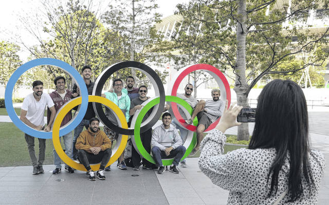 A group of students from Uruguay get their picture taken Saturday with the Olympic Rings outside the Olympic Stadium in Tokyo.