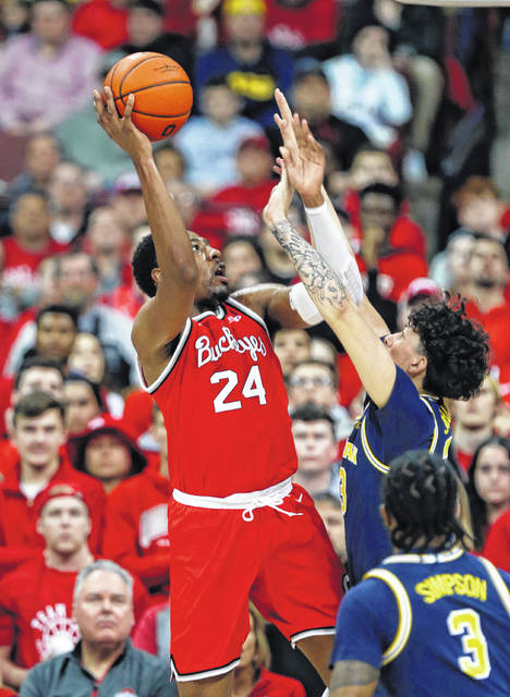 Ohio State forward Andre Wesson, left, goes up to shoot in front of Michigan forward Brandon Johns, center, and guard Zavier Simpson (3) during the first half of an NCAA college basketball game in Columbus, Ohio, Sunday, March 1, 2020. (AP Photo/Paul Vernon)