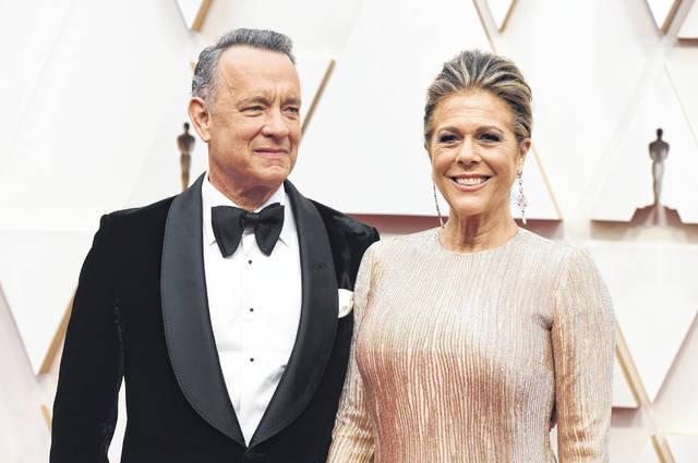 """Tom Hanks, left, and Rita Wilson arrive Feb. 9 at the Oscars at the Dolby Theatre in Los Angeles. The couple tested positive for the coronavirus, the actor said in a statement Wednesday. The 63-year-old actor said they will be """"tested, observed and isolated for as long as public health and safety requires."""""""