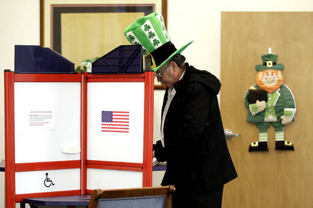 A voter fills out his ballot, taking advantage of early voting, Sunday, March 15, 2020, in Steubenville, Ohio. Elections officials in the four states, Arizona, Florida, Illinois and Ohio, holding presidential primaries next week say they have no plans to postpone voting amid widespread disruptions caused by the coronavirus outbreak. Instead, they are taking extraordinary steps to ensure that voters can cast ballots and polling places are clean. (AP Photo/Gene J. Puskar)