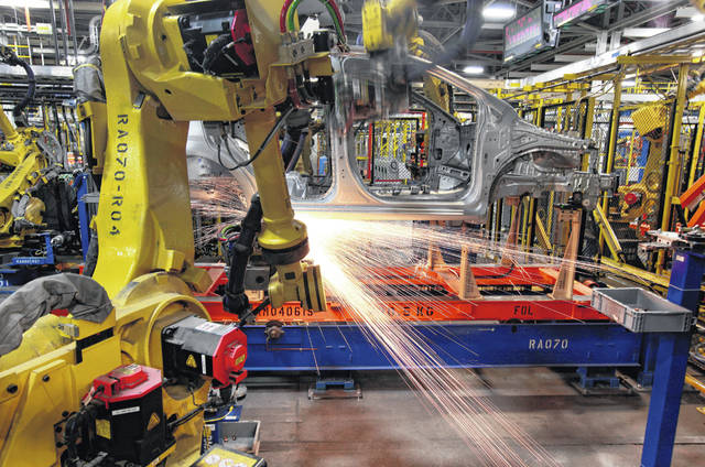 In this May 19, 2011 photo, robots weld a Chevrolet Sonic at the General Motors Orion Assembly plant in Orion Township, Mich. On Friday, President Donald Trump invoked the Korean War-era Defense Production Act, allowing the government to marshal the private sector to fight the COVID-19 pandemic. Although it allows the government to steer factories to overcome shortages, makers of heavy goods such as cars and trucks can't just flip a switch and produce something else.