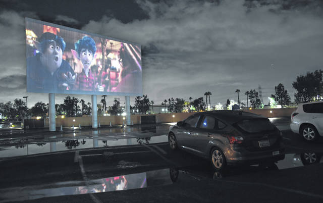 """Viewers in a parked car watch the animated film """"Onward"""" at the Paramount Drive-In Theatres on Thursday in Paramount, Calif. The drive-in theater, long a dwindling nostalgia act in a multiplex world, is experiencing a momentary return to prominence. With nearly all of the nation's movie theaters shuttered due to the pandemic, some drive-in owners think they're in a unique position to give moviegoers a chance to do something out of the house but stay within prudent distance from one another."""