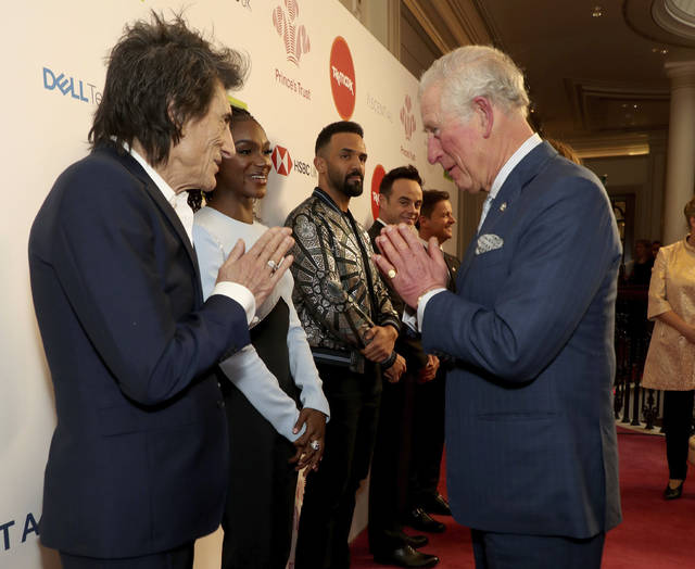 FILE - In this March 11, 2020 file photo, Britain's  Prince Charles, gesture as he greets musician Ronnie Wood as he arrives at the annual Prince's Trust Awards 2020 held at the London Palladium, Wednesday March 25, 2020. Prince Charles, the heir to the British throne, has tested positive for the new coronavirus. The prince's Clarence House office reported on Wednesday, March 25, 2020 that the 71-year-old is showing mild symptoms of COVID-19 and is self-isolating at a royal estate in Scotland. It says his wife Camilla has tested negative. (Yui Mok/PA via AP, File)
