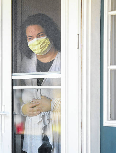 Amy Driscoll looks out the front door of her home Sunday in Hudson after testing positive for COVID-19 on Friday, becoming Summit County's second confirmed case of coronavirus.