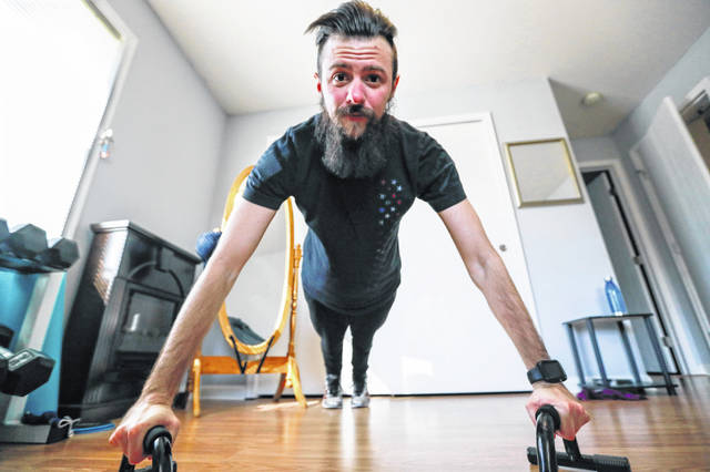 In this Friday, March 13, 2020 photo, Nic Talbott does pushups during one of his workouts in his continuing hopes of being permitted to enlist inn the armed forces at his home in Lisbon, Ohio. Talbott is a plaintiff in one of four lawsuits filed in federal courts challenging a Trump administration policy barring transgender Americans from enlisting in the military.
