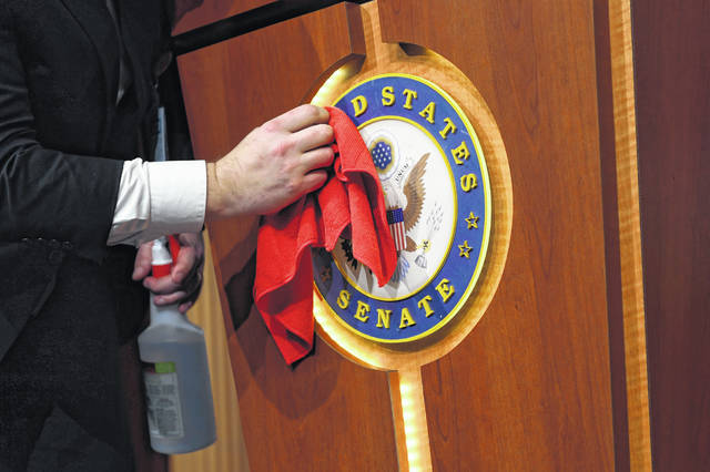 Mike Mastrian, Director of the Senate Radio and Television Gallery, cleans down the podium before a news conference with Senate Majority Leader Mitch McConnell of Ky., on Capitol Hill in Washington, Tuesday, March 17, 2020.