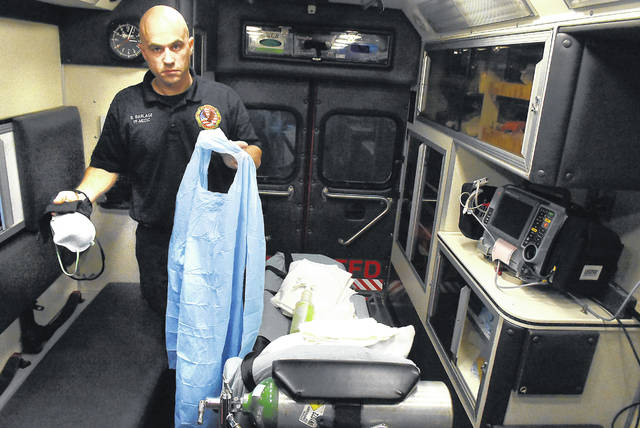 Standing in a rescue vehicle, American Township Firefighter-Medic Brandon Barlage holds a gown, mask, eye protection and latex gloves to be worn during an emergency call for a COVID-19 patient.