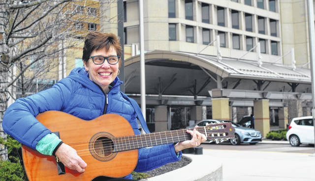 Angie Herzog plays guitar outside of Mercy Health-St. Rita's Medical Center, where she volunteers as part of a music ministry to uplift hospital patients during treatment.