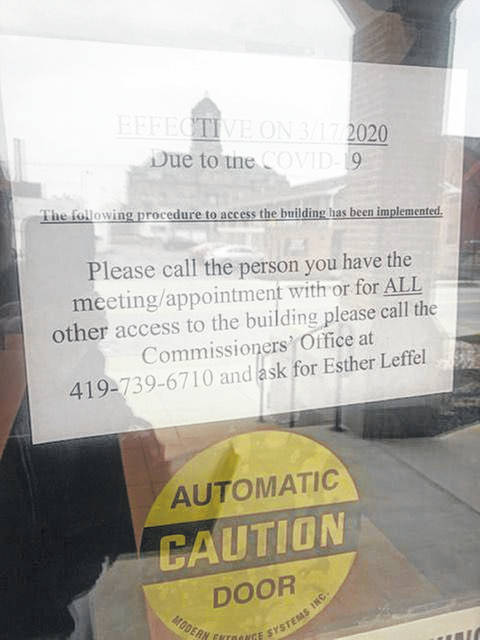 A sign on the door of the Auglaize County Administration Building directs visitors on how to gain access. The doors to the building are locked and visitors are admitted on an appointment basis.