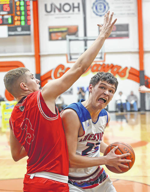 Crestview's Carson Kreischer eyes the basket against Columbus Grove's Tayt Birnesser during a Tuesday night Division IV district semifinal at the Elida Fieldhouse.