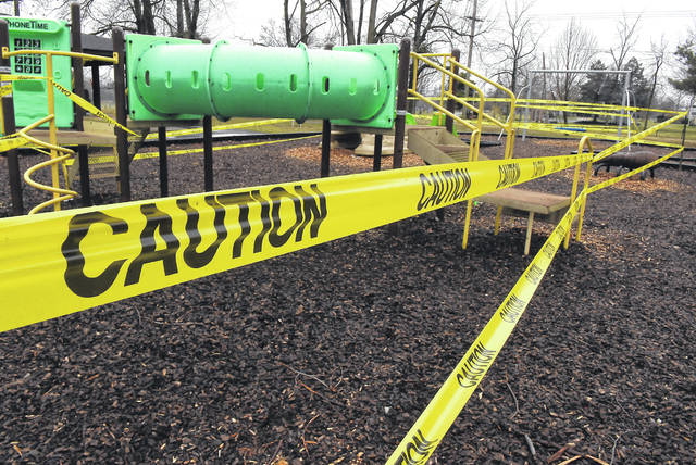 Caution tape is wrapped around playground equipment at Faurot Park in Lima to keep children from playing on it and possibly coming into contact with the new coronavirus.