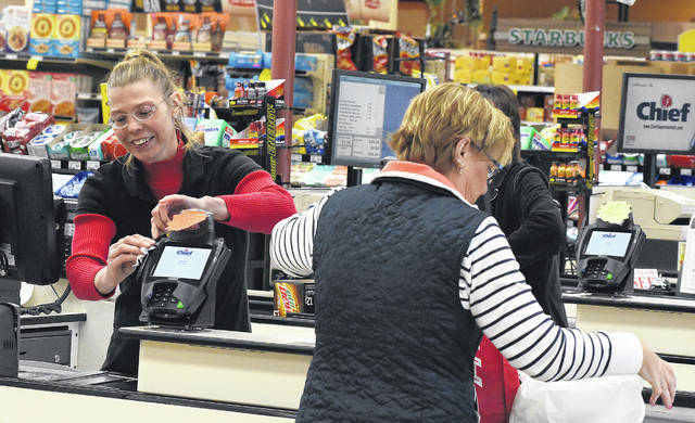 Missy Reed, a cashier at Chief Supermarket on Cable Road in Lima, sanitizes the credit card reader after each customers use in the checkout line.