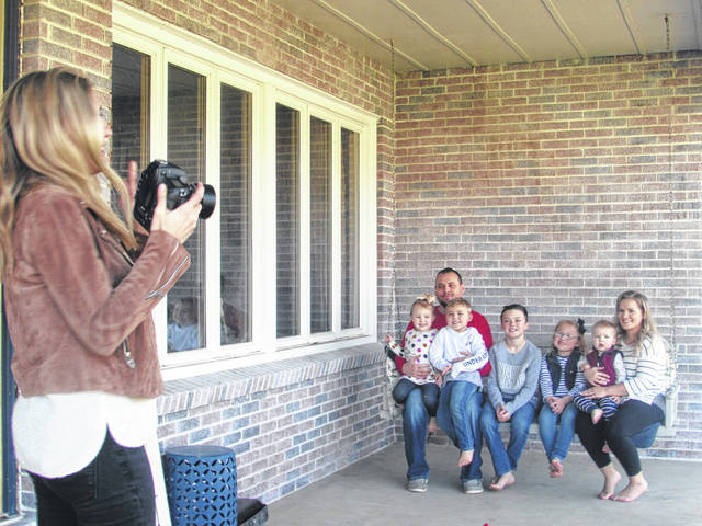Delphos photographer Heather Clark takes a photo of the Hommel family in Delphos Wednesday, from left Lydia, 4, their father, Mitchell, Camden, 5, Maddox, 11, Elianna, 7, Traeden, 1, and their mother, Elizabeth.