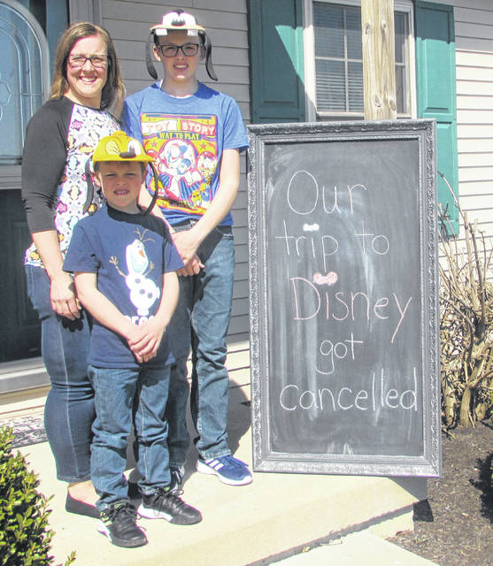 Amanda Arnold and her sons Kolton, 6, and Austin, 12 stand next to a sign they made when their plans were changed due to the novel coronavirus.