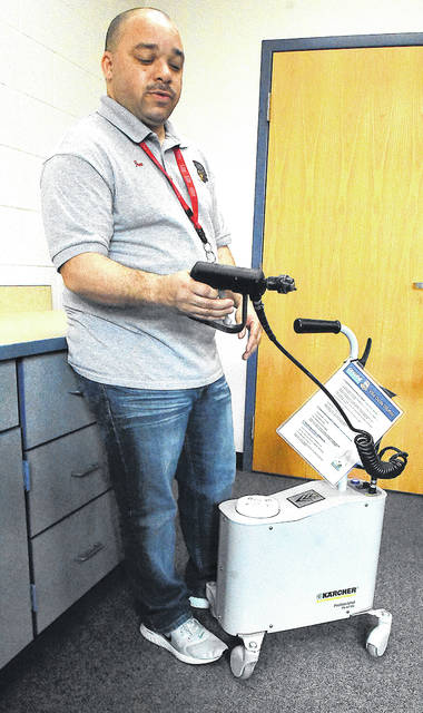Jon Sigman of the South Science and Technology Magnet School maintenance department displays a spray mist machine that will be used to sanitize the building on Monday.