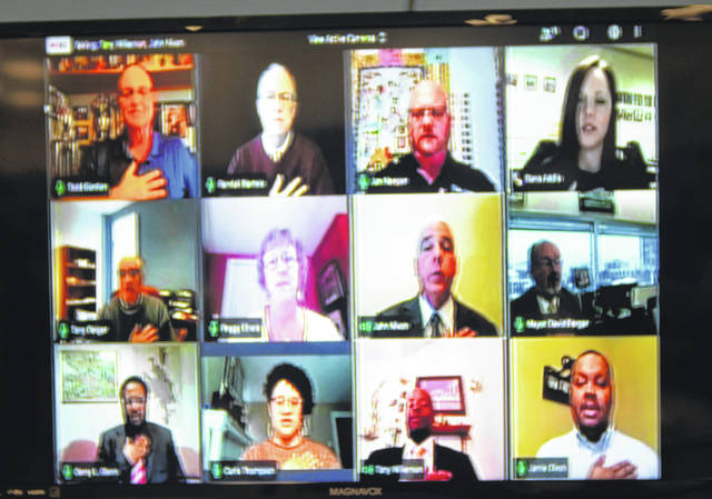 Lima City Councilors and city officials recite the pledge of allegiance during council's first teleconferenced public meeting. While most councilors sit at home, a few backdrops can be easily matched to offices in the city's municipal building.