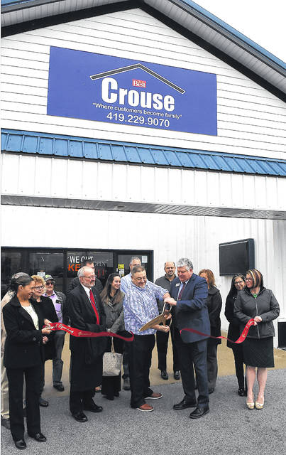 Marvin Schwartz, owner of Crouse Lumber, and Jed Metzger, president of the Lima/Allen County Chamber of Commerce, hold a ribbon cutting ceremony outside the hardware store on Wednesday to celebrate Crouse Lumber's rebranding.